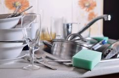 A huge pile of unwashed dishes in the kitchen sink and on the co. Untertop. A lot of utensils and kitchen appliances before washing. The concept of daily cooking stock photography