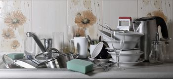 A huge pile of unwashed dishes in the kitchen sink and on the countertop. A lot of utensils and kitchen appliances before washing. The concept of daily cooking royalty free stock photography