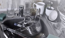 A huge pile of unwashed dishes in the kitchen sink and on the countertop. A lot of utensils and kitchen appliances before washing. The concept of daily cooking stock photography