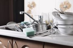 A huge pile of unwashed dishes in the kitchen sink and on the countertop. A lot of utensils and kitchen appliances before washing. The concept of daily cooking royalty free stock photos