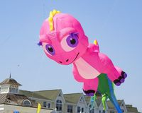 Huge Pink Dinosaur Kite In-Flight. Large big flying kites colorful air wind variety sunny day blue skies activity sport fun outside outdoors festival beach royalty free stock images