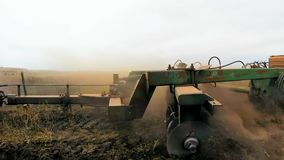 A huge plow plows the field. The camera follows his movement stock video footage