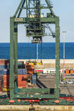 Huge port crane surrounded by containers Royalty Free Stock Photos