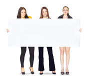 Huge poster held by three cute business girls Stock Photography