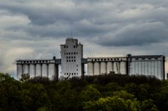 A huge, powerful factory, towering above the green forest.. A huge, powerful factory, towering above the green forest. The factory rises to the sky Stock Photography