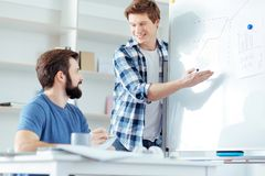Smart male colleagues visualizing ideas. Huge profit. Attractive two male colleagues staring at each other while men standing near white boar and pointing at it Royalty Free Stock Photos