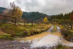 Huge puddle on the country road. Wooden fence along the path. deep autumn in mountainous countryside stock photos