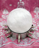 Huge Quartz Crystal Ball on Wild Steel Stand. Wicked divination display, features a huge genuine milky quartz crystal sitting on  steel spike stand, with red Royalty Free Stock Photography