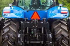 Huge rear wheels of the blue new tractor Stock Photos