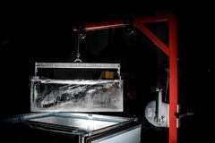 Huge rectangular ice piece produced at the factory. Huge rectangular ice piece produced at the modern factory on the dark black indoors background stock photography