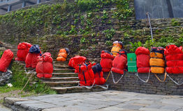 Huge red backpacks for mountain expedition on stairs. Porter Mountaineering equipment. Nepal, Annapurna Base Camp track Royalty Free Stock Photography