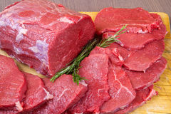 Huge red meat chunk and steak on wood table Stock Photo