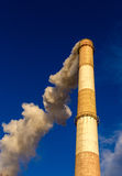 Huge red and white chimney rising high above towards a blue sky belches out v Stock Photo