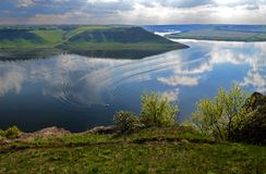 The huge river Dniester flows between high steep hills covered with spring lush green grass against the blue sky royalty free stock photography