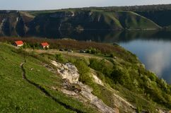 The huge river Dniester flows between high steep hills covered with spring lush green grass against the blue sky stock photos