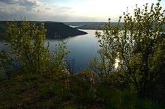 The huge river Dniester flows between high steep hills covered with spring lush green grass against the blue sky royalty free stock images