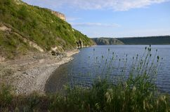 The huge river Dniester flows between high steep hills covered with spring lush green grass against the blue sky royalty free stock photos