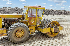 Huge road roller with spikes is compacting soil at construction Stock Photos