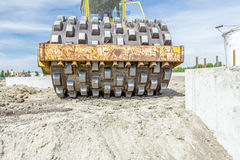 Huge road roller with spikes is compacting soil at construction Royalty Free Stock Photography