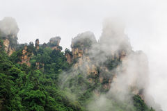 Huge Rock Mountains Surrounded by Green Trees and White Mist Clouds. Epic Mountain Landscape Royalty Free Stock Photo