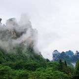 Huge Rock Mountains Surrounded by Green Trees and White Mist Clouds. Epic Mountain Landscape Royalty Free Stock Photos