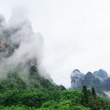 Huge Rock Mountains Surrounded by Green Trees and White Mist Clouds. Epic Mountain Landscape Stock Photo