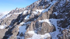 Huge rocks covered with snow. Ledges from the snowy mountains. Cliffs and large rocks. Dangerous terrain. Drone view from the top and side. The sun`s rays on stock images