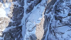 Huge rocks covered with snow. Ledges from the snowy mountains. Cliffs and large rocks. Dangerous terrain. Drone view from the top and side. The sun`s rays on stock photo