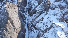 Huge rocks covered with snow. Ledges from the snowy mountains. Cliffs and large rocks. Dangerous terrain. Drone view from the top and side. The sun`s rays on royalty free stock photos