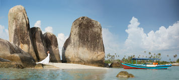 Huge rocks in Indonesia, blue ship and white dress woman Royalty Free Stock Photo