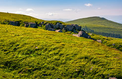 Huge rocks on top of mountain ridge. Mountain summer landscape. meadow with huge rocks among the grass on top of the hillside near the peak of mountain ridge Stock Images