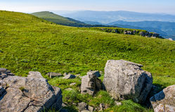 Huge rocks on top of mountain ridge. Mountain summer landscape. meadow with huge rocks among the grass on top of the hillside near the peak of mountain ridge Stock Photo