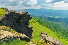 Huge rocky formations on the grassy hills. Beautiful mountain landscape in late summer on a cloudy day. location Runa mountain, Ukraine royalty free stock photos