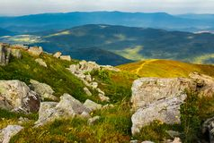 Huge rocky formations on the grassy hills. Beautiful mountain landscape in late summer on a cloudy day. location Runa mountain, Ukraine royalty free stock photo
