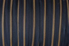 Huge rolls of zippers. Laps of black and gold metal furnishing f. Or clothing or goods making manufacture stock images