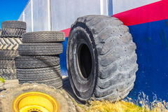 Huge Rubber Tire With Stacks of Normal Tires Royalty Free Stock Photography