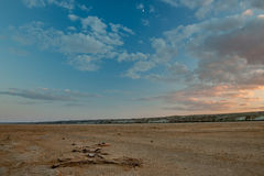 Huge sand and clay beach of the Aral sea. On the shore lay sticks, shells, twigs. On a blue sky moon beautifully illuminated the clouds. Clouds of white and pink Royalty Free Stock Photo