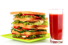 Huge sandwich. And glass of tomato juice on white background Stock Image