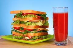 Huge sandwich and  tomato juice Stock Photos
