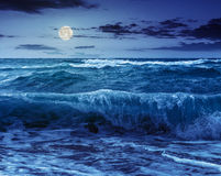 Huge sea waves running on sandy beach at night Stock Images