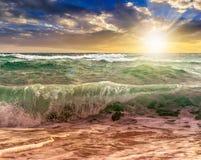 Huge sea waves running on sandy beach at sunset Royalty Free Stock Photos