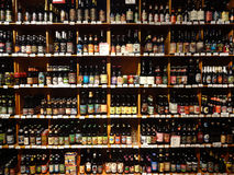 A Huge Selection of Beer on Supermarket Shelves. A huge selection of beer bottles lined up and on display in a specialty supermarket, in its wine and beer ( stock image