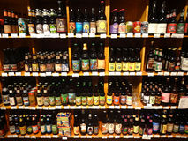A Huge Selection of Beer on Supermarket Shelves. A huge selection of beer bottles lined up and on display in a specialty supermarket, in its wine and beer ( royalty free stock photography
