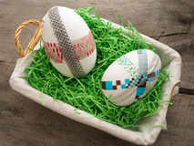 Huge selfmade easter eggs in a basket with easter grass. Two selfmade colored taped easter eggs on a wooden table with easter grass Stock Image