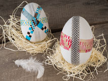 Huge selfmade easter eggs in a nest. Two selfmade colored taped easter eggs in a nest with a feather Stock Images