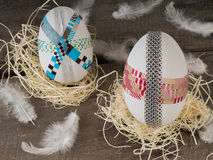 Huge selfmade easter eggs in a nest. Two selfmade colored taped easter eggs in a nest with a feather Royalty Free Stock Photography