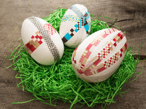 Huge selfmade easter eggs in a nest. Two selfmade colored taped easter eggs on a wooden table with easter grass Stock Photo