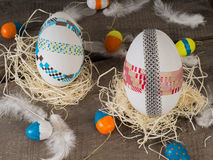 Huge selfmade easter eggs with some small colored eggs. Two selfmade big colored taped easter eggs in a nest with painted small eggs Royalty Free Stock Photos