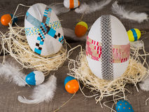 Huge selfmade easter eggs with some small colored eggs. Two selfmade big colored taped easter eggs in a nest with painted small eggs Stock Photos
