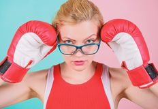 A huge sense of self confidence. Sportswoman with nerdy look. Pretty woman in glasses and boxing gloves. Cute boxer girl royalty free stock image